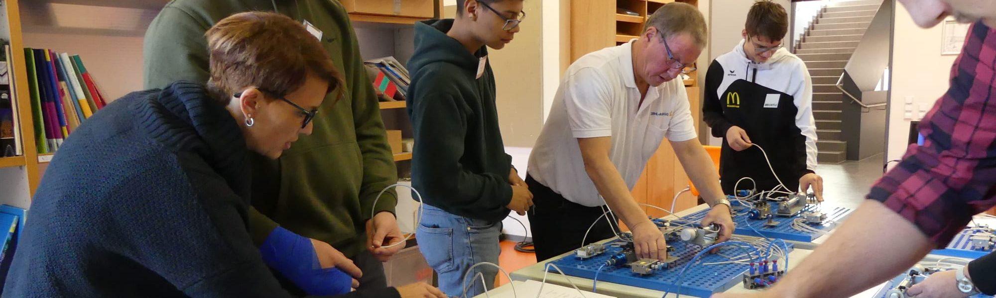 Mehrere Schüler mit einem Ausbilder im Gespräch